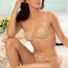 Woman wearing Lise Charmel Fleur Aphrodite underwired padded plunge bra in skin colour